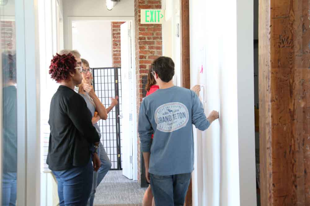 Group reviewing sticky notes on wall