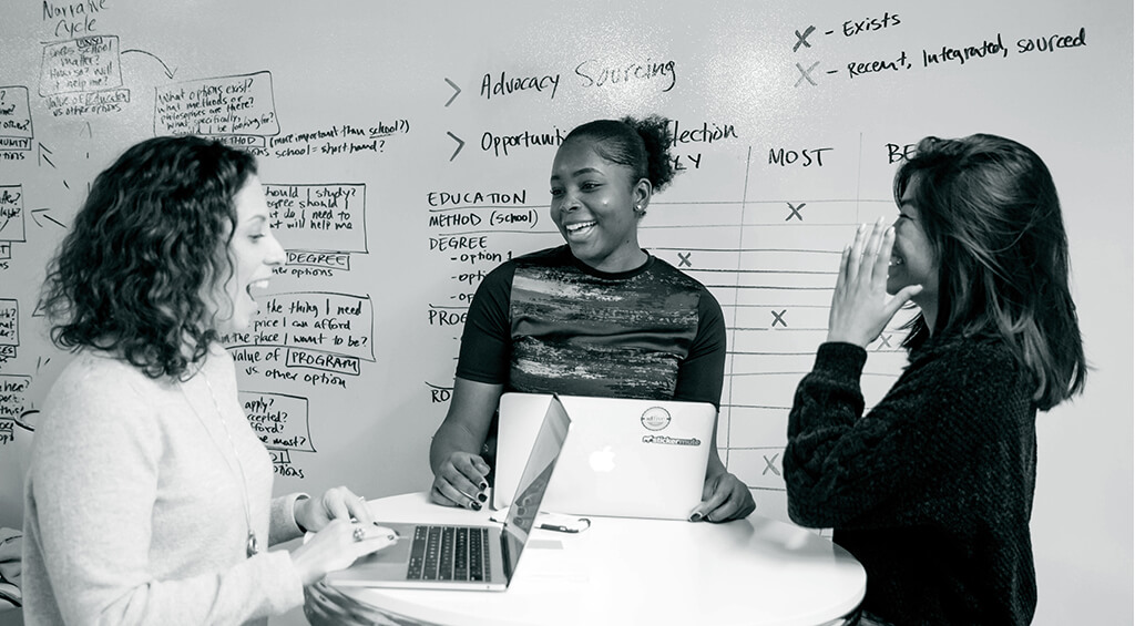 Three idfive team members discuss a campaign while standing at a circular table, the whiteboard wall behind them filled with notes.